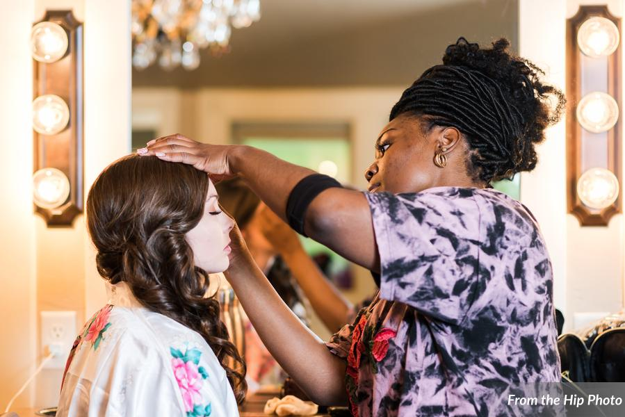 Wedding stylist creating beautiful hair and makeup for a bride