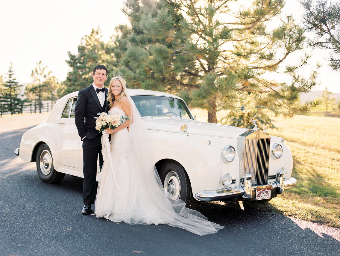 Couple with a Rolls Royce limousine on their wedding day