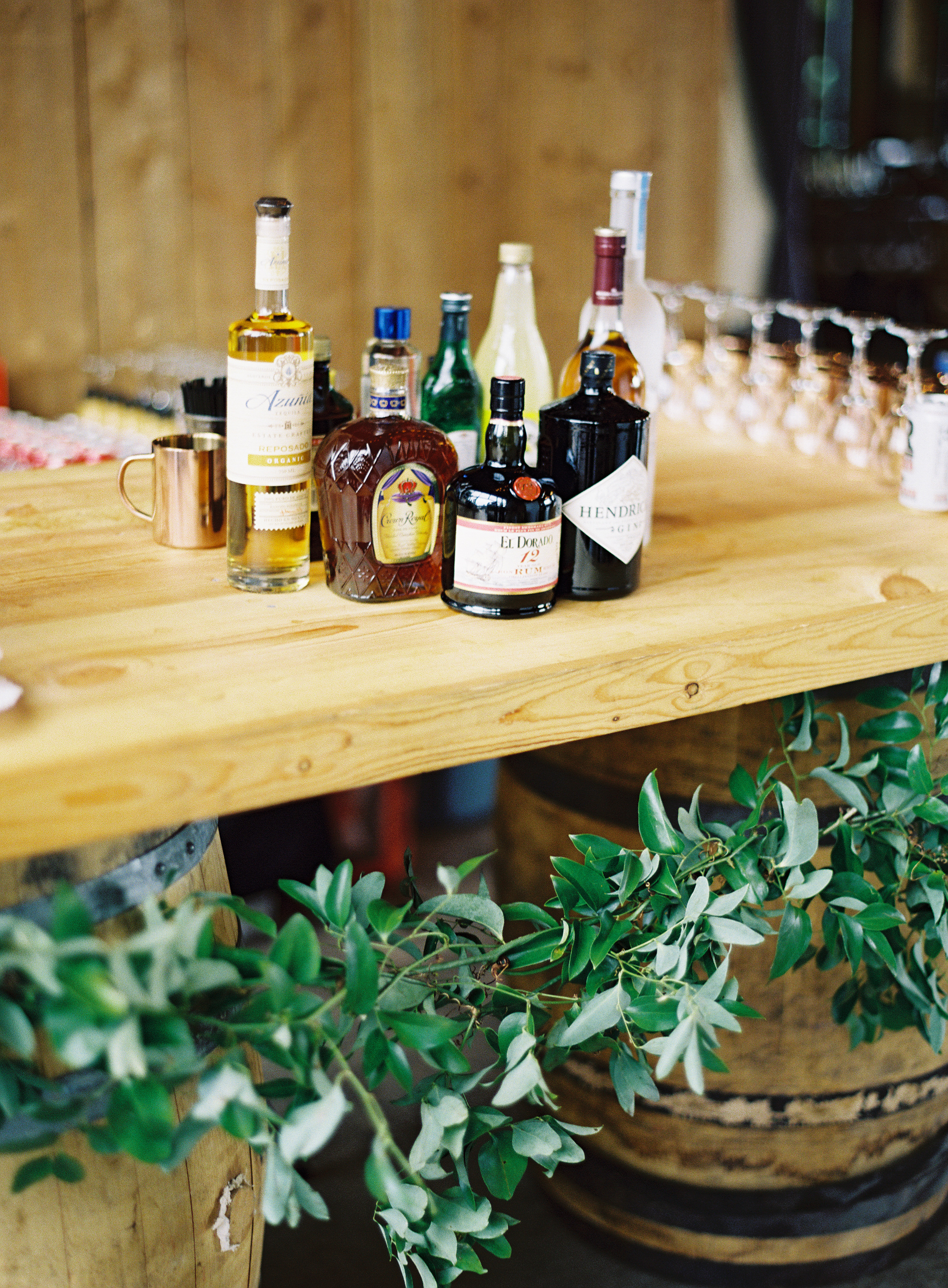 Liquor bottles at wedding on rustic table with barrels and greenery