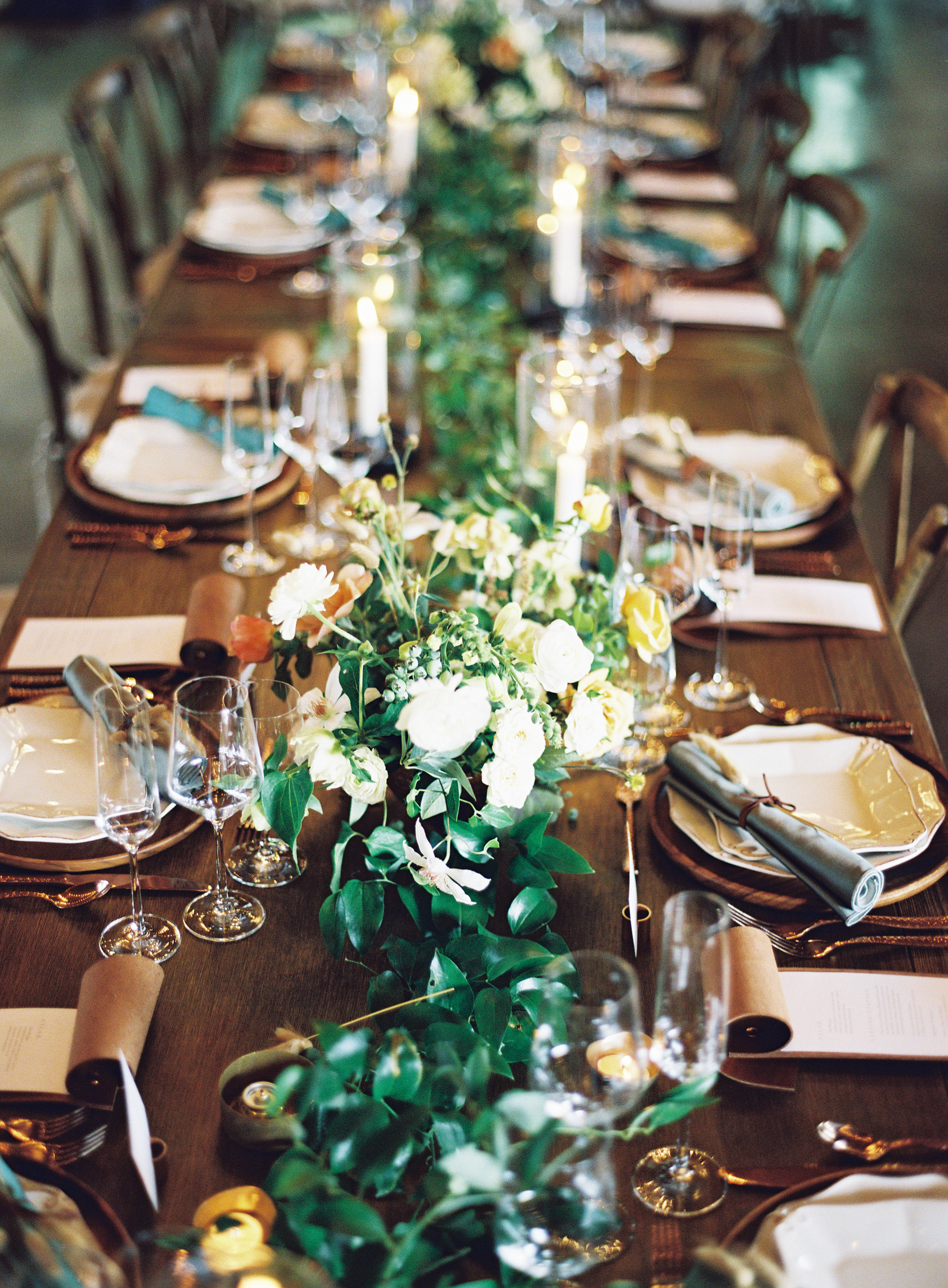 Elegant long table setting with candles and greenery