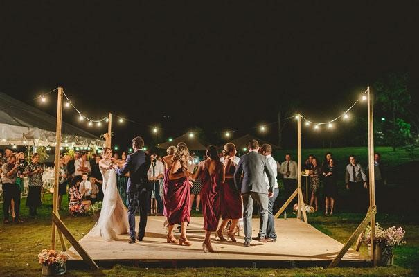 Bride, Groom and wedding guests dancing on outdoor dance floor